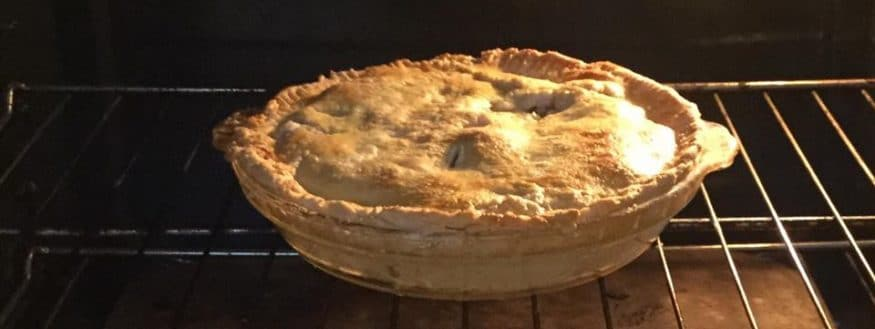 baked apple pie in the oven on a rack