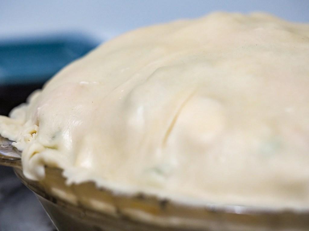 chicken pot pie unbaked in pie pan on top of stove