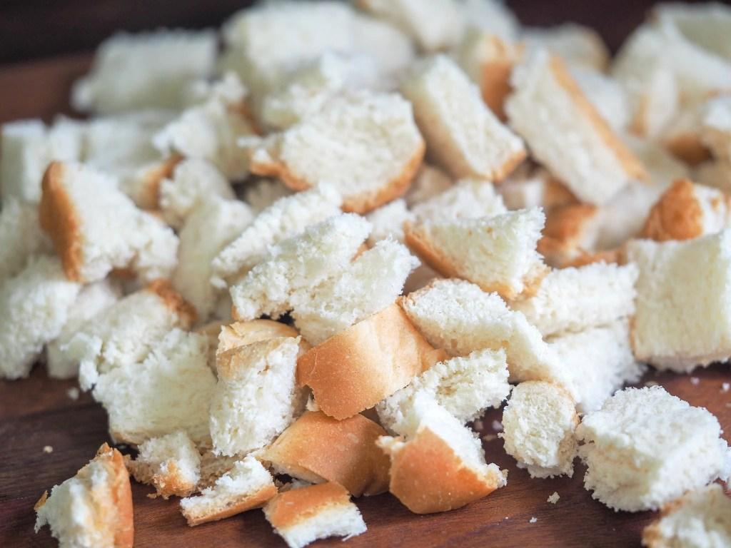 cubed white bread sitting on a dark cutting board