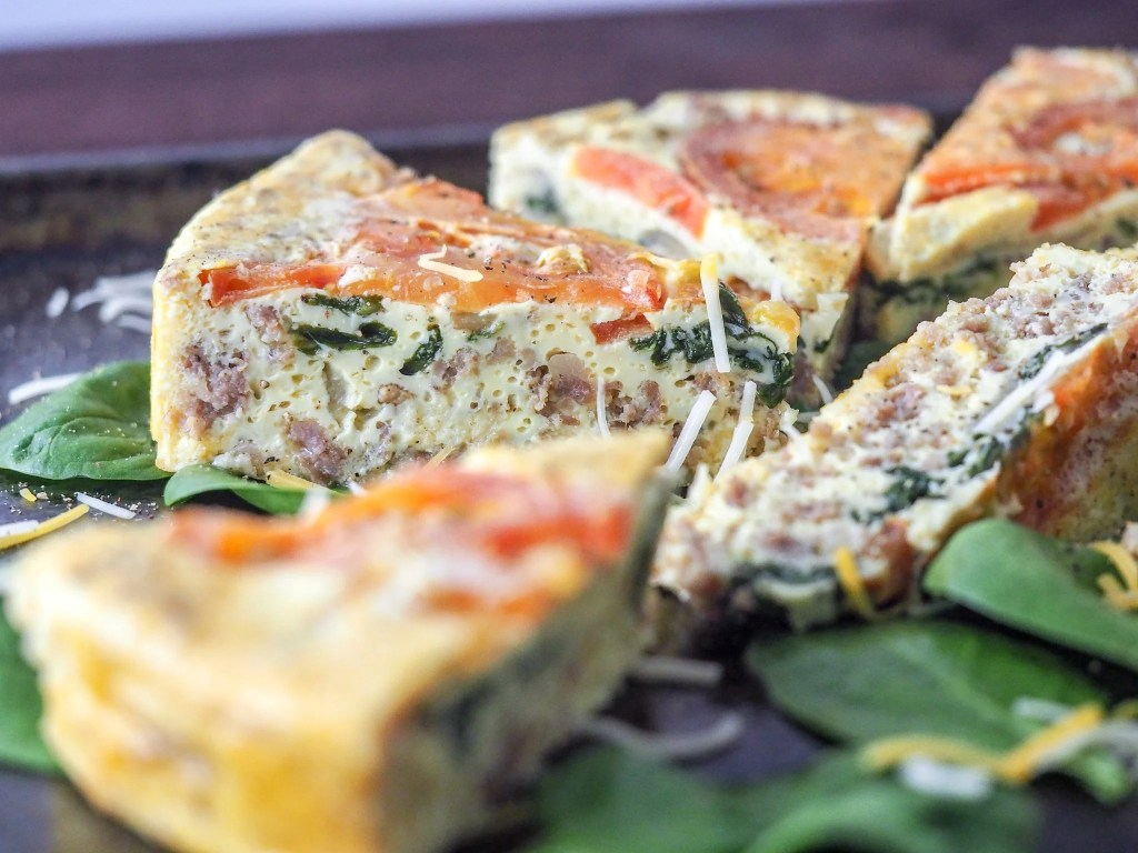 sliced frittata pieces on a bed of spinach lying on a baking sheet
