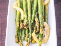 overhead view of steamed asparagus facing downwards on white plate