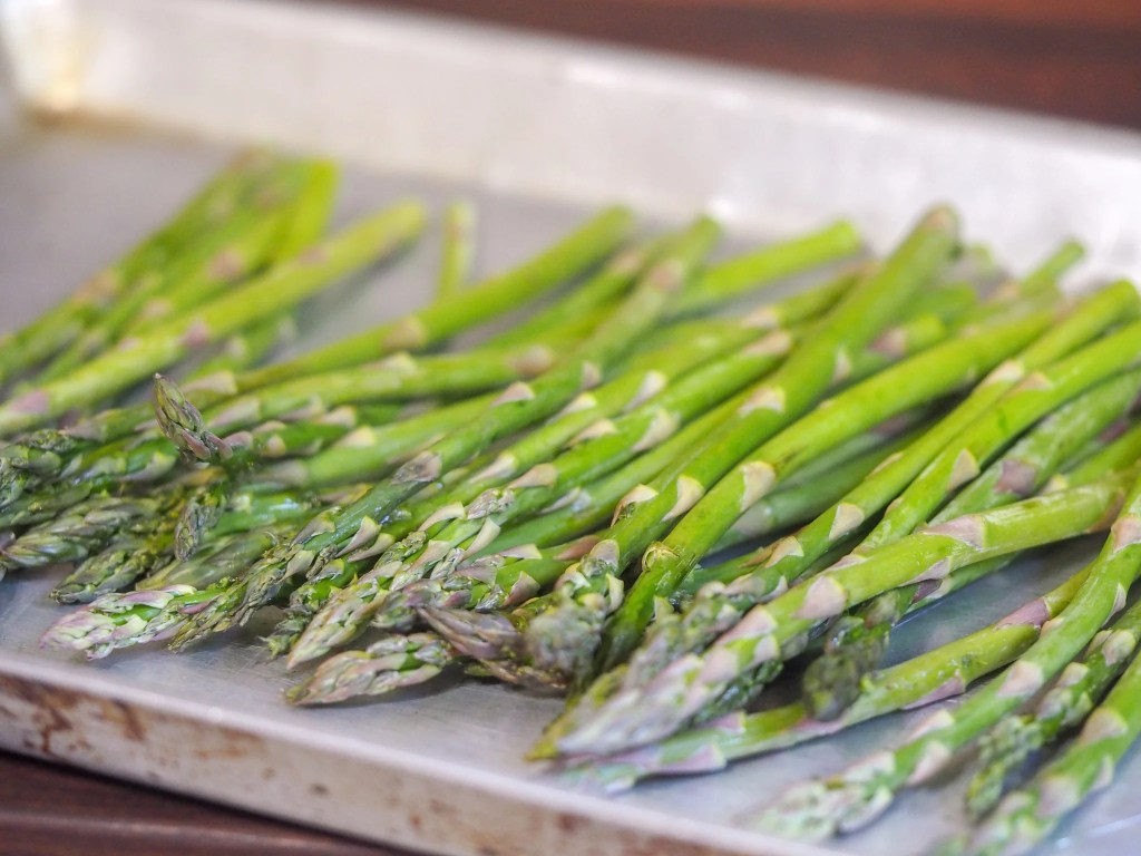 trimmed asparagus spears laying on an aluminum tray