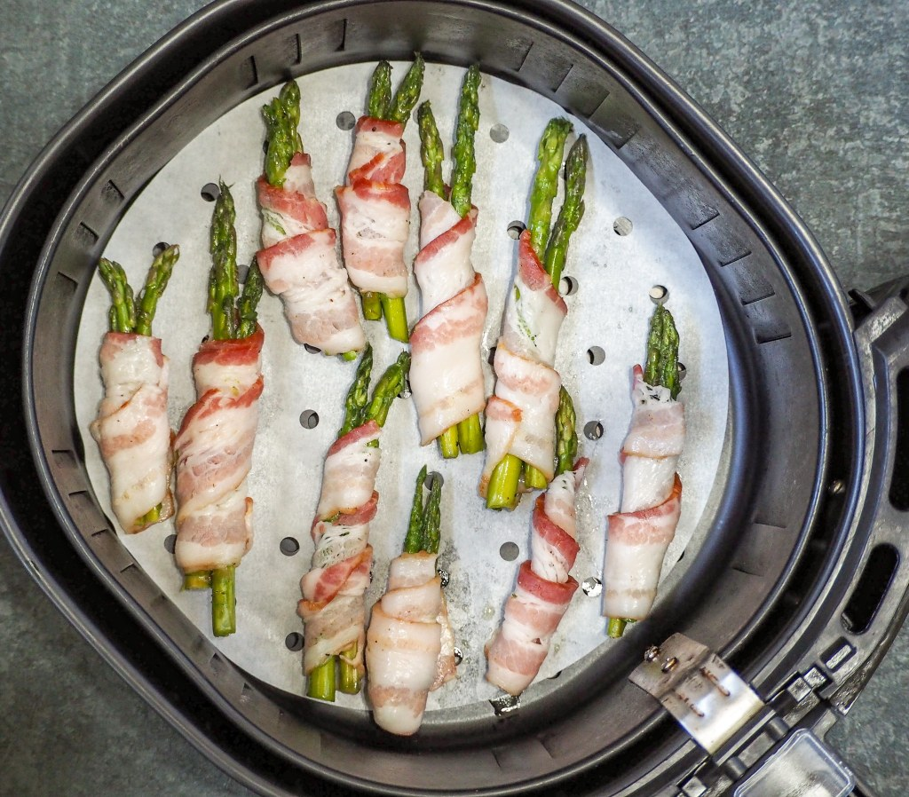 overhead shot of bacon wrapped asparagus in an air fryer basket
