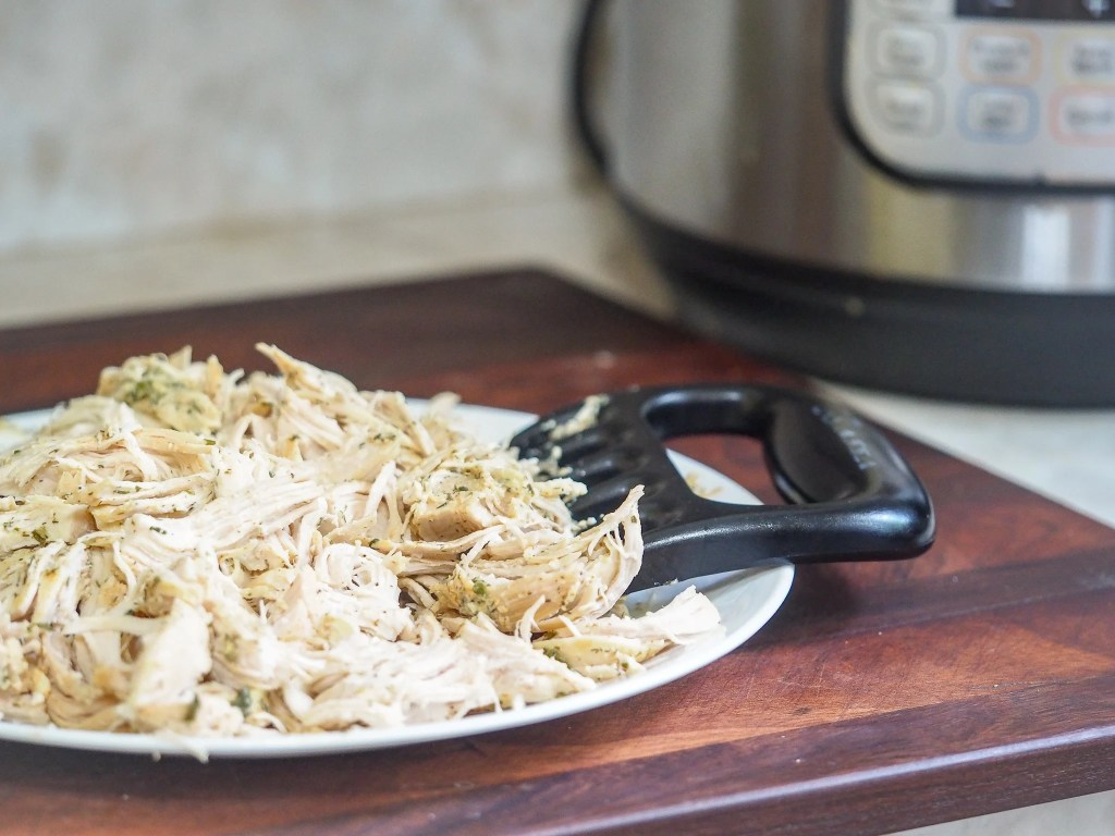 shredded cooked chicken on plate with shredding claw with instant pot in right background