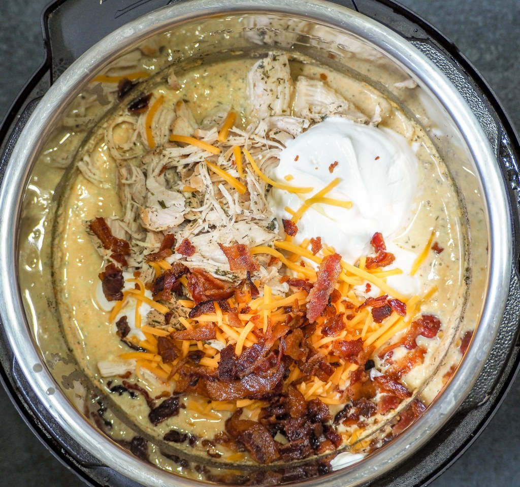 overhead shot of instant pot with cooked chicken cheese crumbled bacon mayo and sour cream
