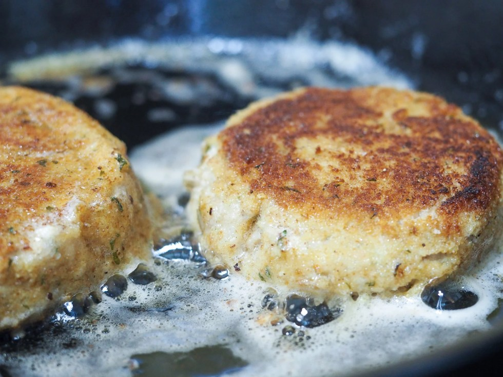 close view of salmon patties being fried in a cast iron pan