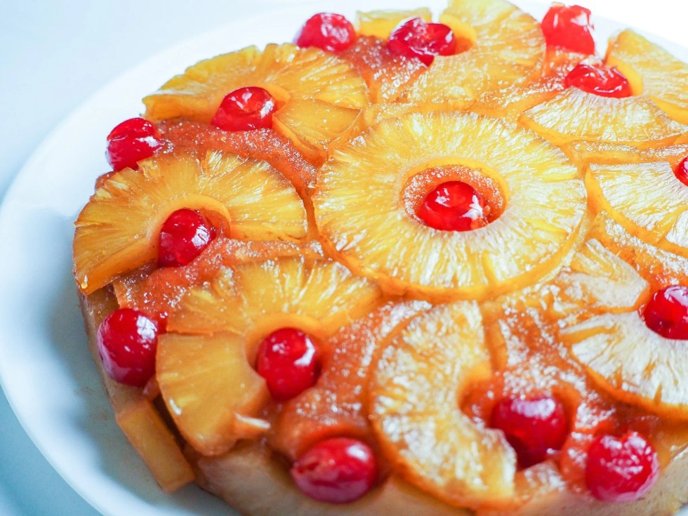pineapple upside down cake on plate topped with sliced pineapple and cherries
