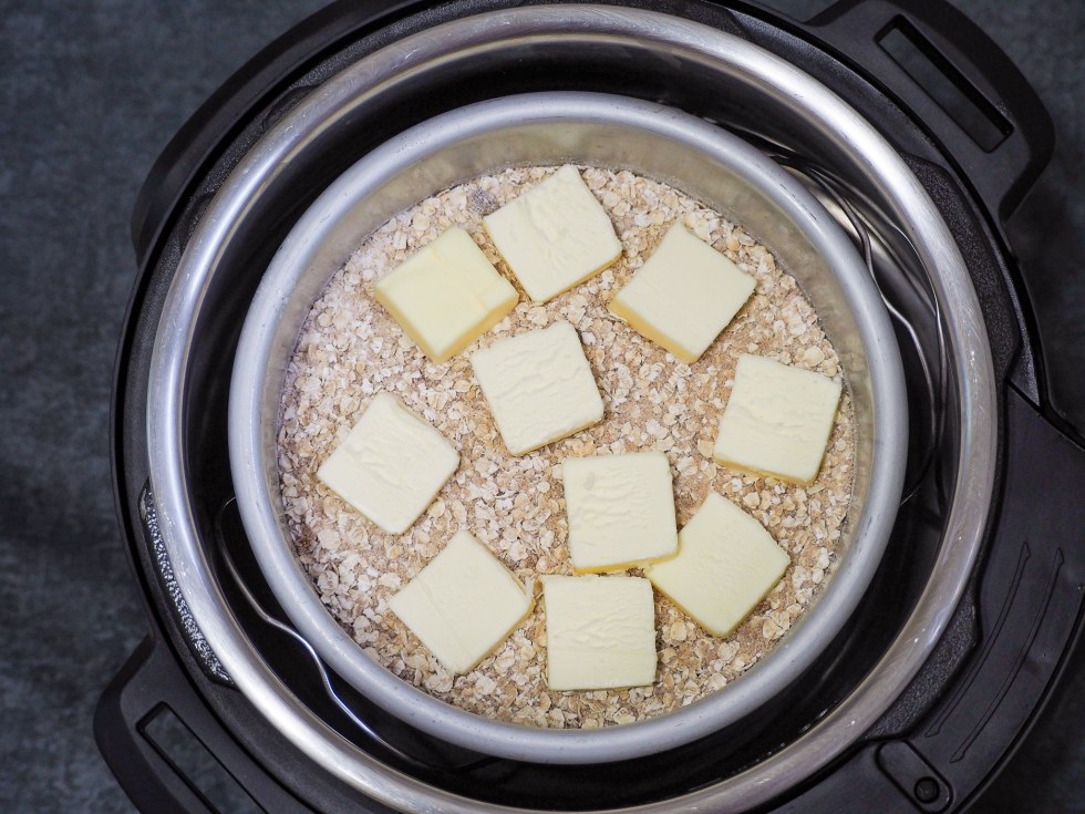 overhead view of uncooked peach crisp in instant pot with butter pats on top
