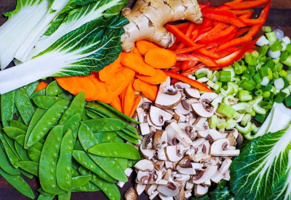 overhead shot of snow peas and other sliced vegetables like carrots, red bell pepper, celery, and mushrooms