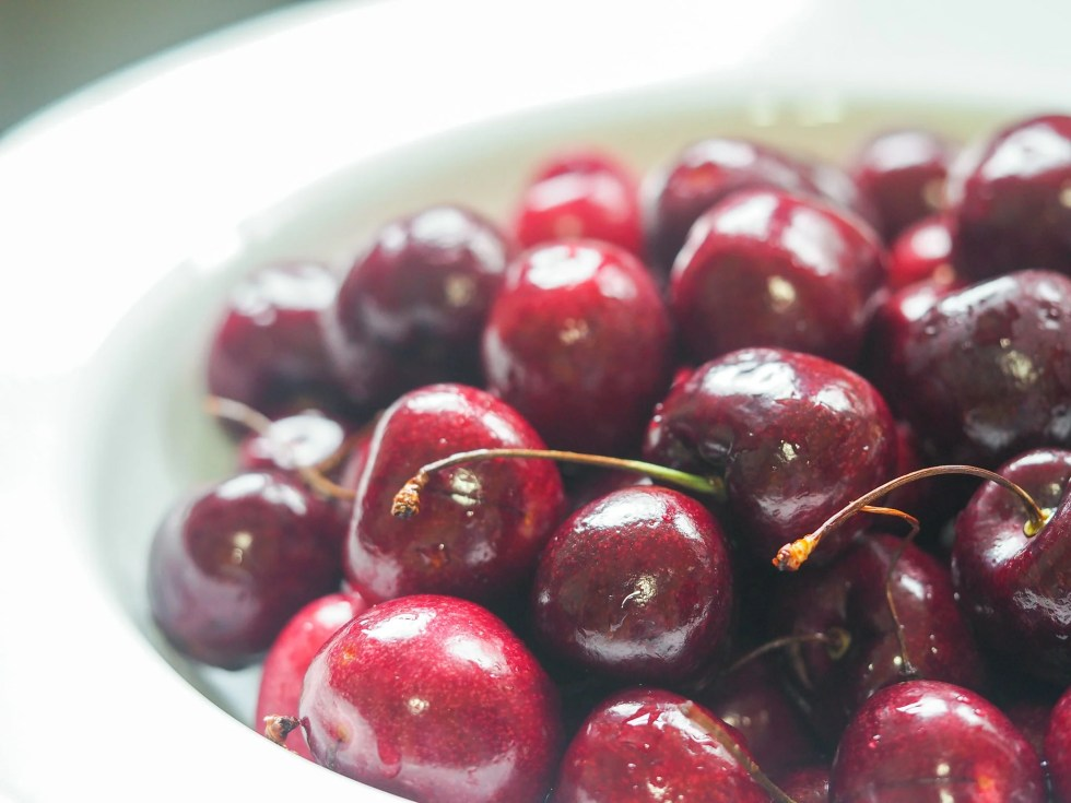 close up of fresh cherries in a colander