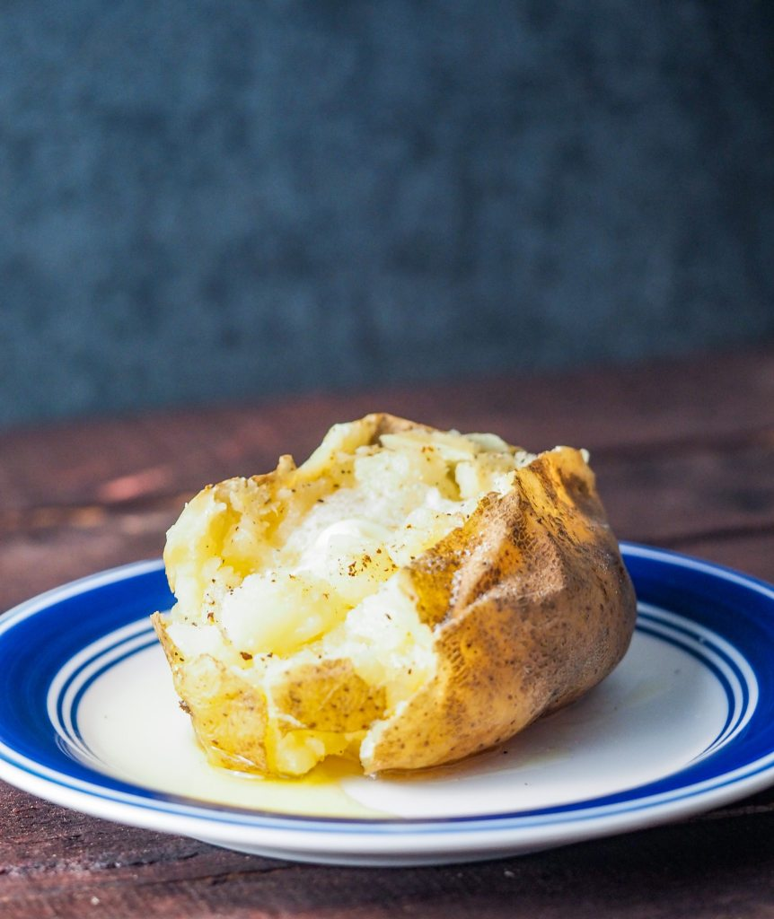 baked potato with butter on plate view from side