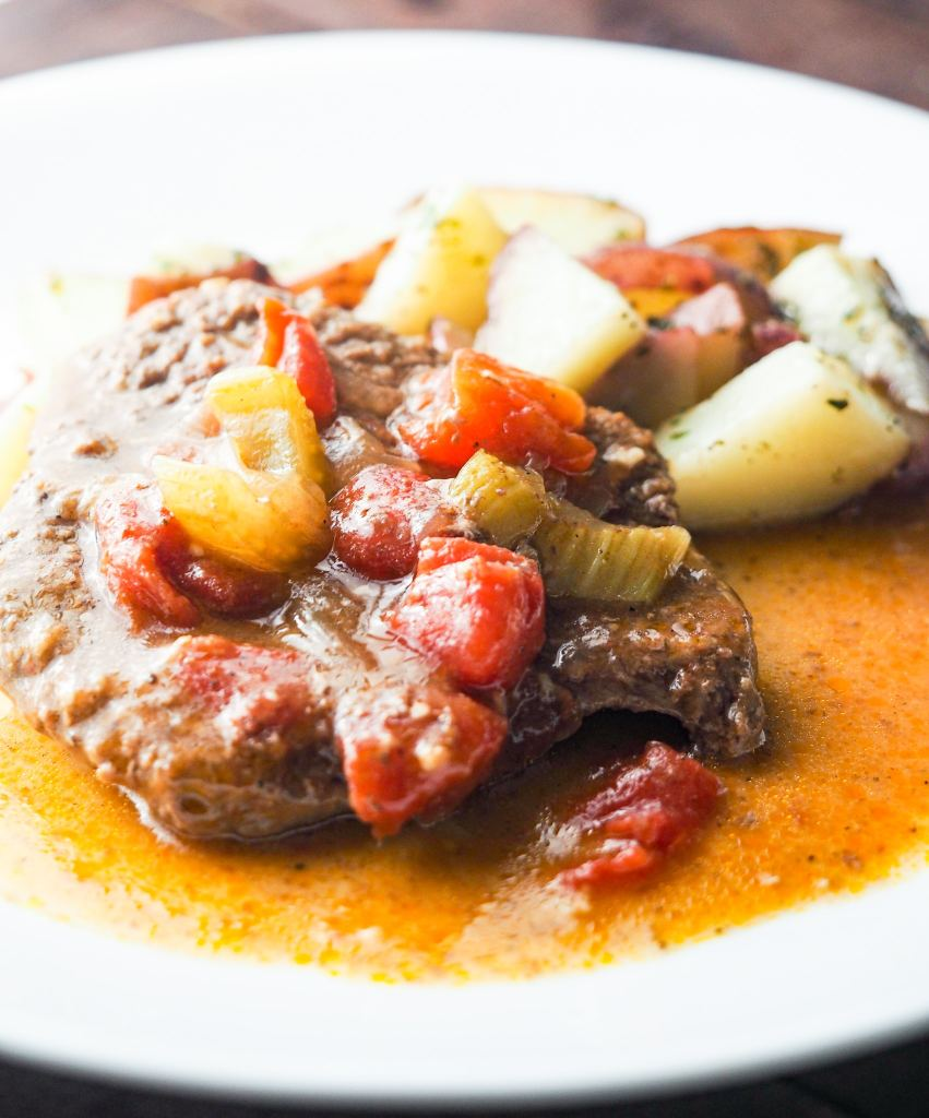 swiss steak with tomatoes on white plate with parslied potatoes