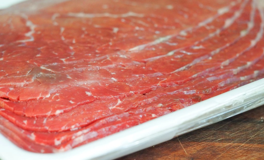 milanesa cut beef in butcher wrapping on cutting board