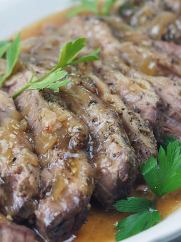close side view of sliced beef brisket on white platter with gravy sprinked with flat leaf parsley
