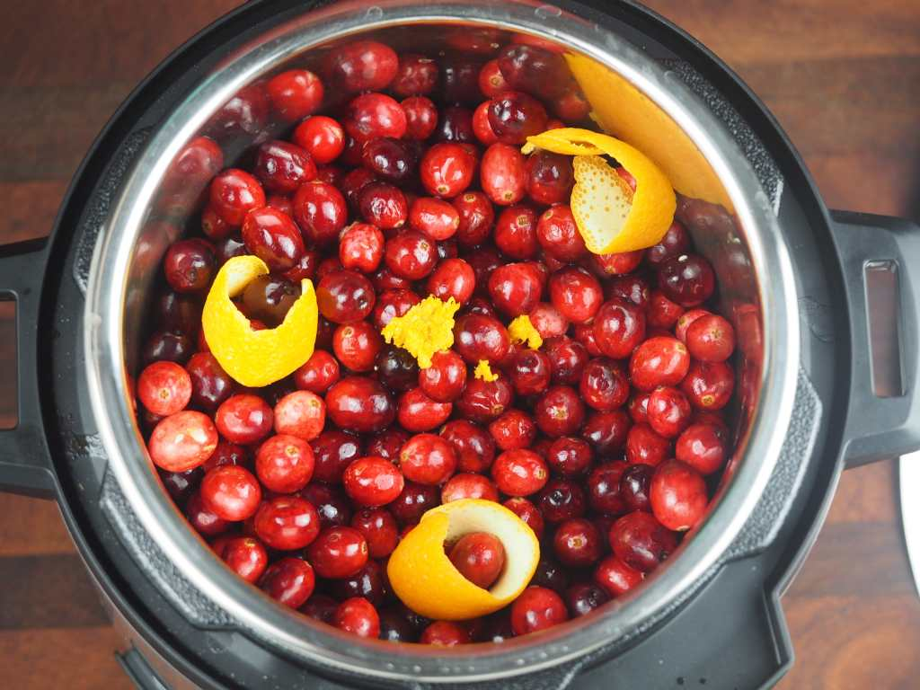 overhead view of cranberries with orange zest and peels in an Instant Pot