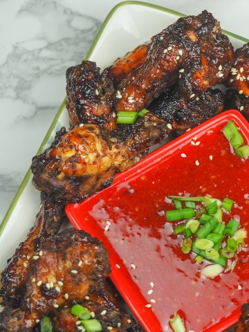 overhead view of cooked chicken wings on platter set to the right at an angle with sweet chili dipping sauce in the middle