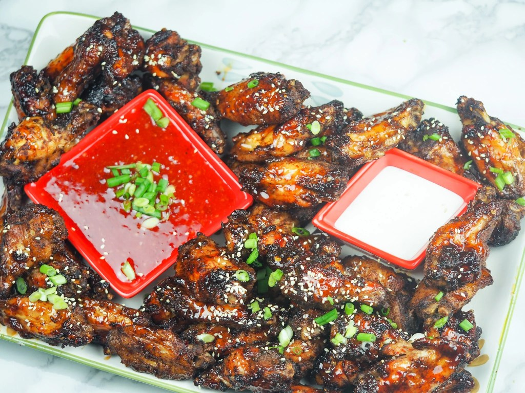 overhead shot of chicken wings on platter with chili sauce and blue cheese for dipping