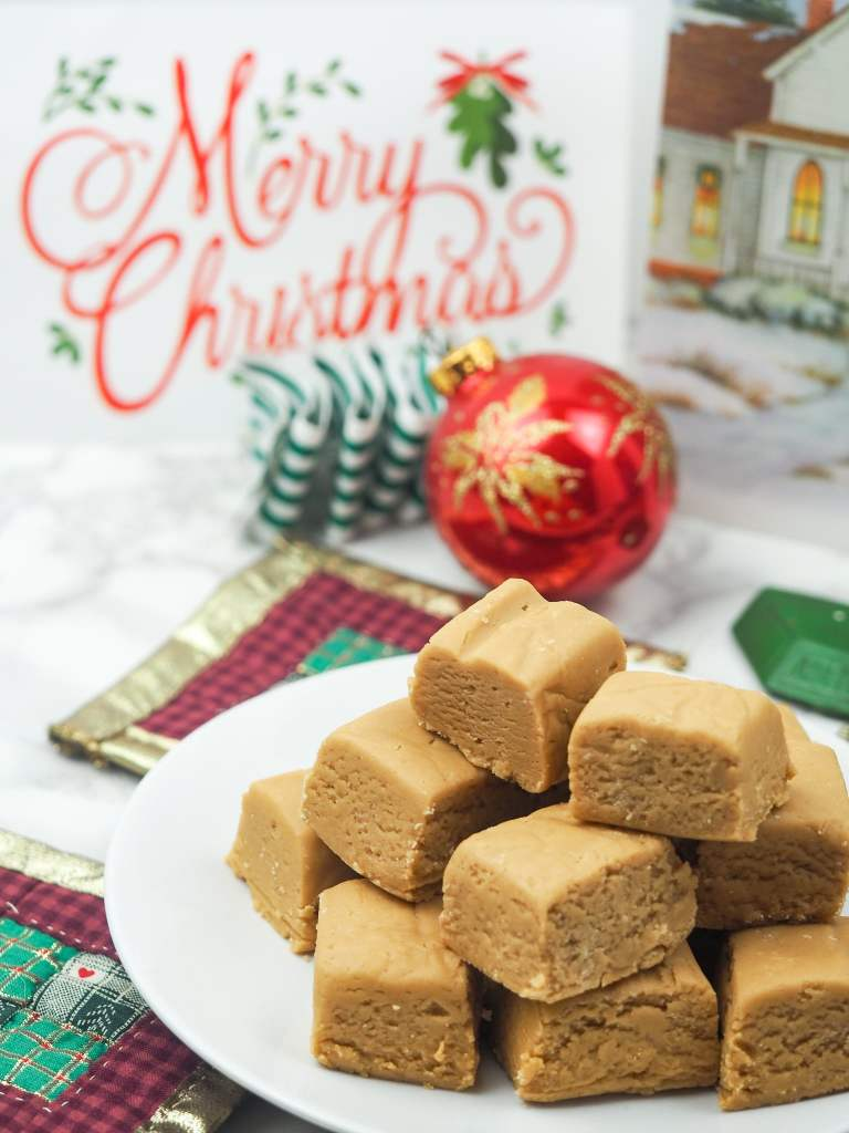 peanut butter fudge on plate in front of christmas cards and ornaments