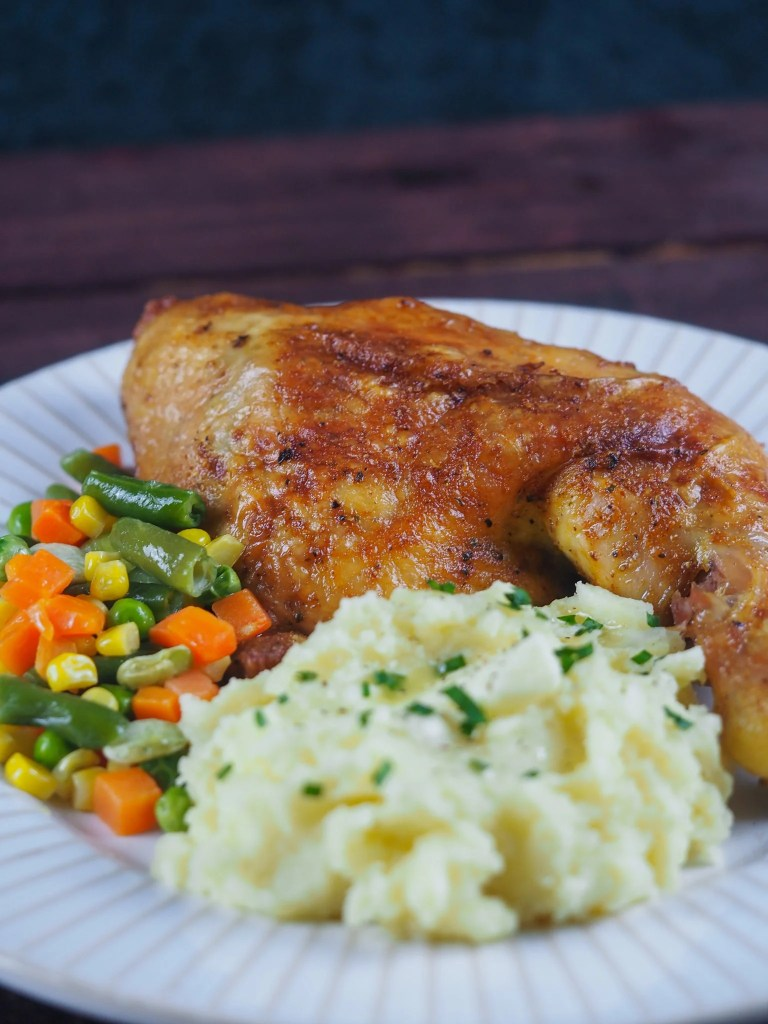 Baked chicken leg quarter on white plate with mashed potatoes and mixed vegetables.