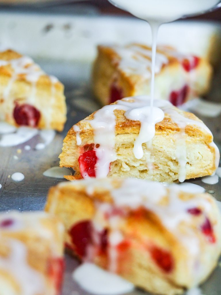baked cherry scones on cookie sheet being drizzled with lemon glaze