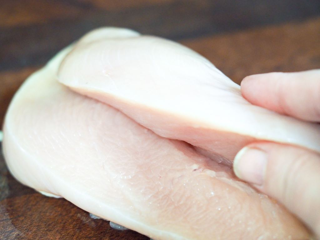 boneless skinless chicken breast on cutting board cut in half to butterfly lengthwise