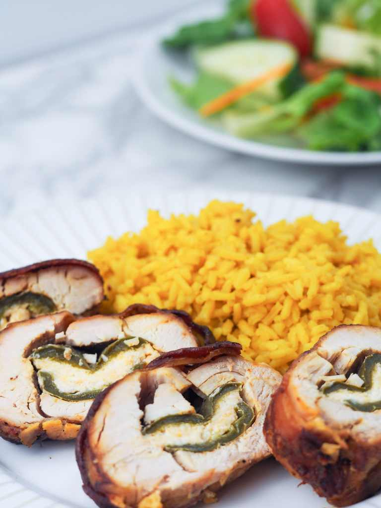 sliced jalapeno stuffed chicken breast on plate with yellow rice, plate of green salad in background off to the right