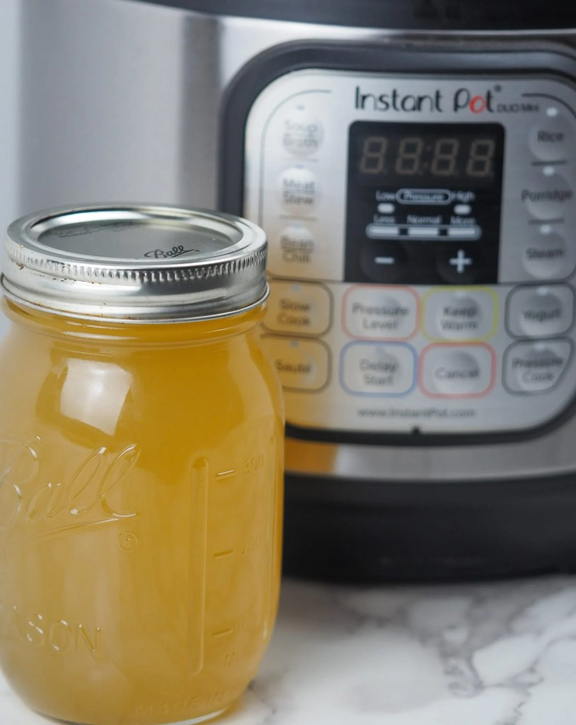 chicken bone broth in jar on marble counter top with Instant Pot in background