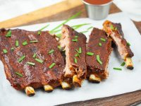 ribs on cutting board on top of parchment paper
