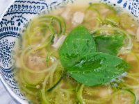 close view of zoodle chicken soup topped with basil leaves