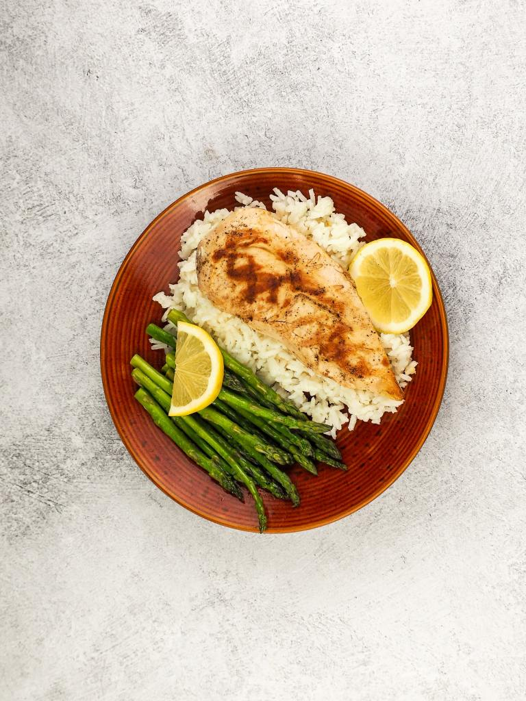 cooked lemon chicken with grill marks on bed of jasmine rice with asparagus and lemon slices on brown plate
