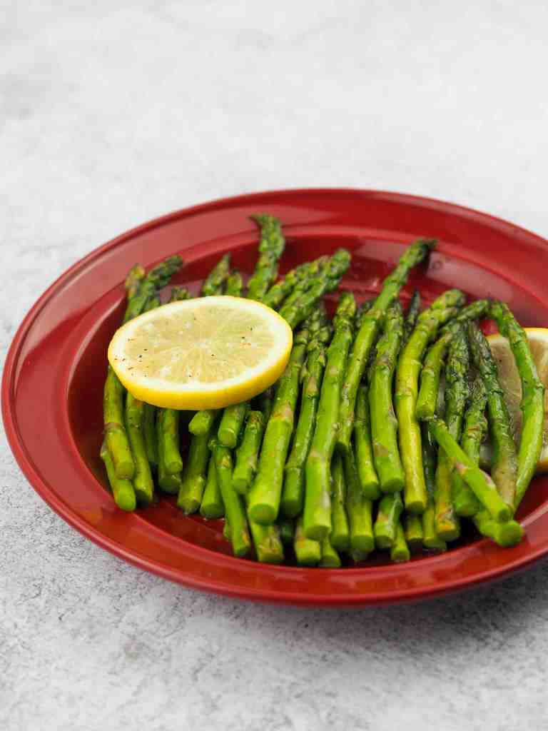 cooked asparagus on red dinner plate with two slices of lemon