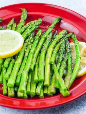 cooked asparagus on red dinner plate with two slices of lemon on each side