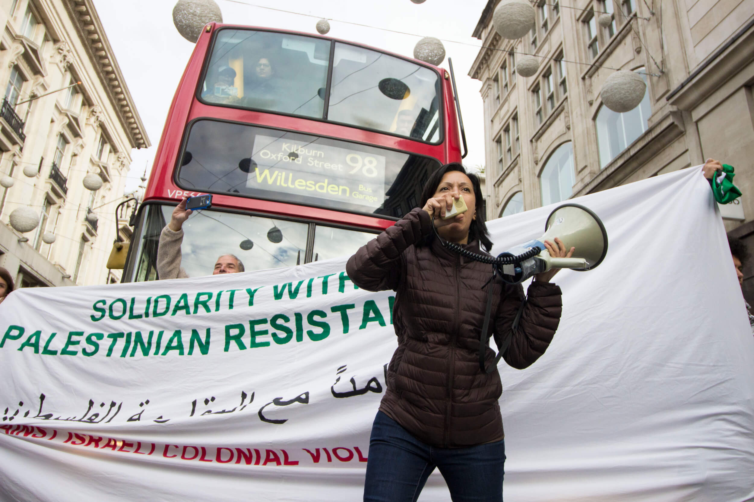 Palestinian artist and activist Rafeef Ziadah stops traffic on Oxford Street. (Photo: Sara Anna)