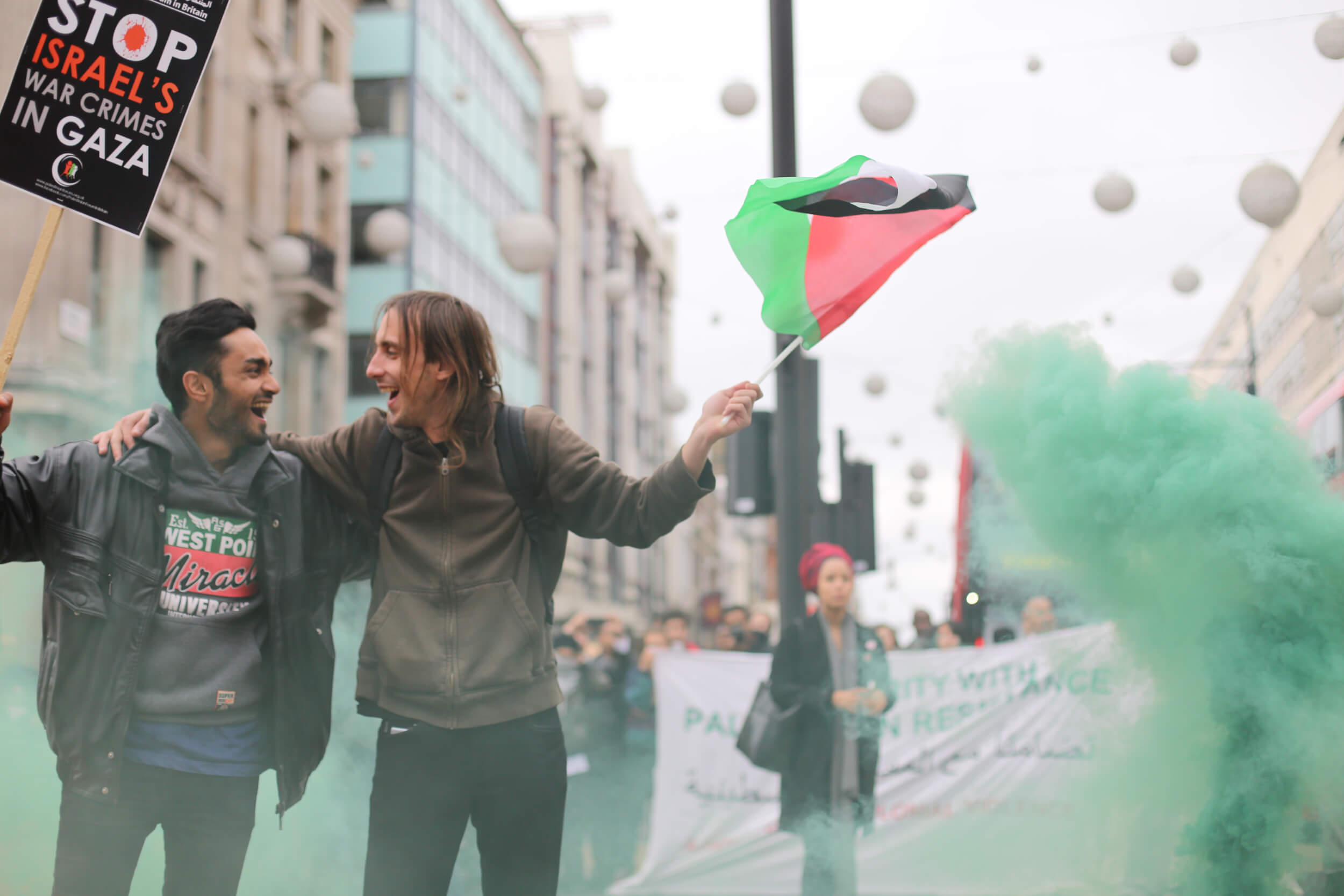 London Palestine Action protestors set off red and green smoke bombs, two of the colours of the Palestinian flag, while blocking traffic at Oxford Circus. (Photo: Sara Anna)