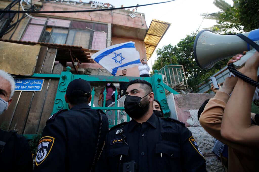 Israeli forces protect Israeli settlers outside a house in the Palestinian neighborhood of Sheikh Jarrah in occupied East Jerusalem on April 16, 2021. (Photo: Jamal Awad/APA Images)
