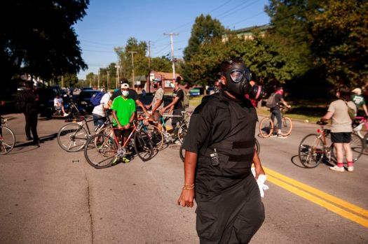 A protester protects themself with a gas mask as they march near the outside of the race track.