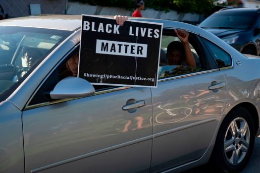 A person holds a Black Lives Matter sign from their car.