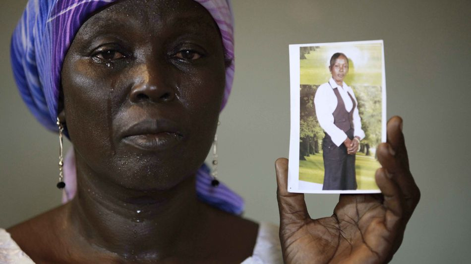 Martha Mark, the mother of kidnapped school girl Monica Mark cries as she displays her photo, in the family house, in Chibok, Nigeria.