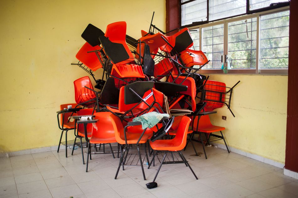 Chairs sit in a pile int he corner of a class room that has been cleared out in the Ayotzinapa normalista school.