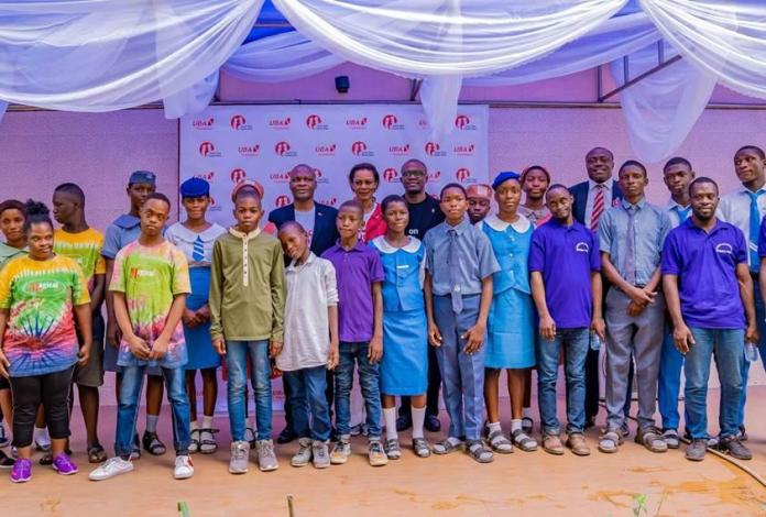 Executive Director, United Bank for Africa(UBA) Plc, Mr. Ayoku Liadi; CEO, UBA Foundation, Mrs. Bola Atta; Head, Brand Management, UBA Plc, Mr. Lashe Osoba, flanked by students of various schools during the 2nd edition of UBA Foundation's 'Each One, Teach One' initiative where UBA Staff teach and assist the less privileged, especially students and people living with disabilities across Africa, held in Lagos on Friday.