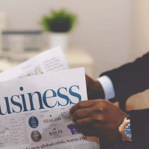 Picture showing a gentleman reading a business newspaper