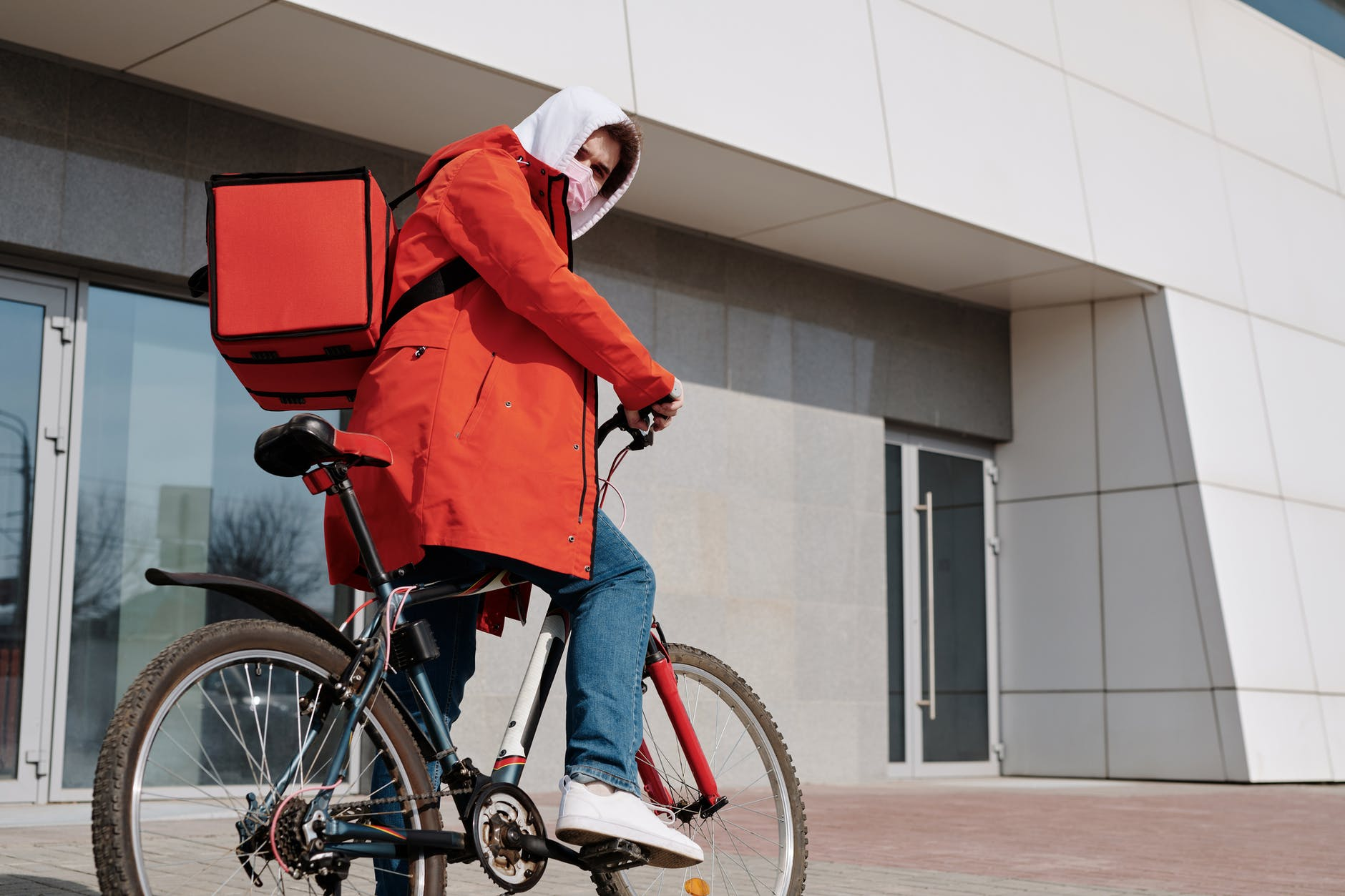 delivery man with a face mask riding a bicycle