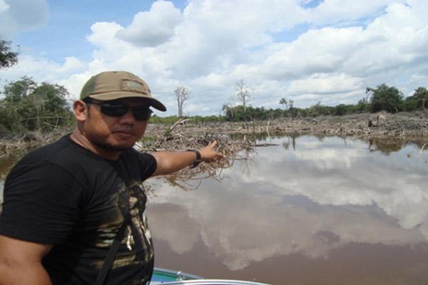 Rayendra, Chairman of theSintang Fishing Club, shows Lake Jentawang near Nanga Ketungau Village, which has allegedly been damaged by waste from palm oil companies. Photo: Yusrizal
