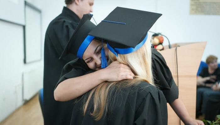 Erfolgreich sein, 2 Frauen im Doktorhut umarmen sich