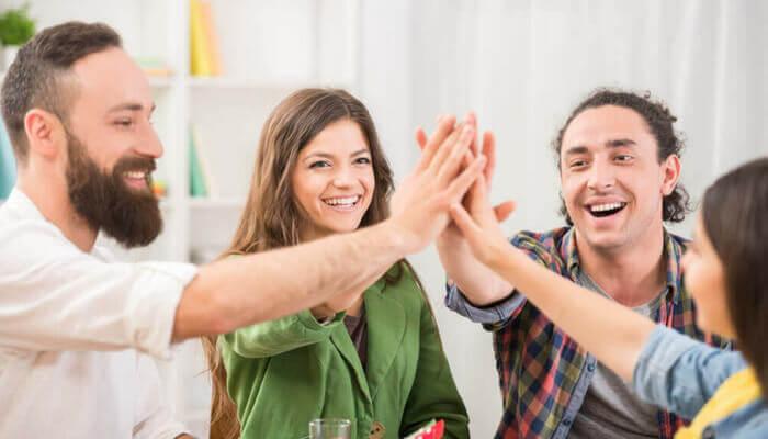Selbstbewusstsein steigern, 4 junge Menschen an einem Tisch