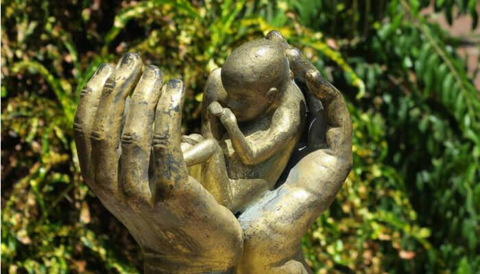 Bronzestatue Hände die einen Embryo halten