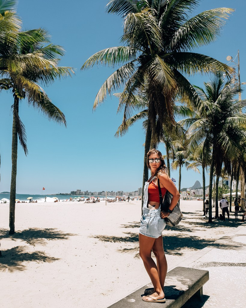 Girl standing on the palm tree lined sidewalk next to Copacabana beach