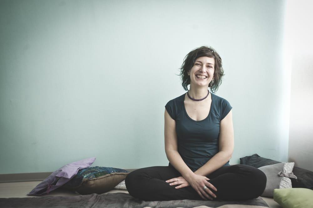 donna (io) che sorride. Seduta a terra con un gomito appoggiato al ginocchio piegato