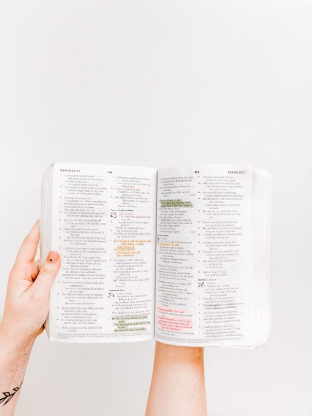 someone holding open a Bible showing the Psalms, with various verses highlighted