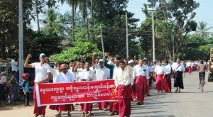 students' parents in Mon traditional suits hold signs while marching in Kyaikmayaw Town